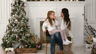 Young mother talking on the phone with slightly bored daughter sitting on her lap next to the xmas tree
