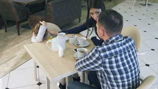 Young parents try to calm their little frustrated daughter in cafe