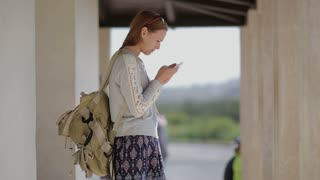 Young pretty girl tourist at the bus stop useing smartphone with backpack. Countryside. Europe