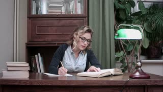 Young student in glasses sitting at a table and writing notes from a book