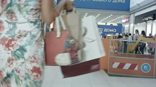 Young woman carrying shopping bags while walking through the shopping center
