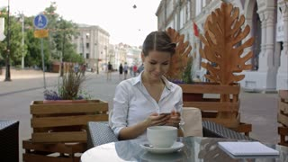 Young woman drinking coffee and using her mobile phone in a outdoor cafe