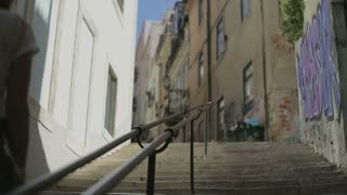 young woman goes up by ledder on street of Lisbon