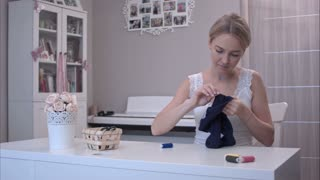 Young woman mending childrens clothes