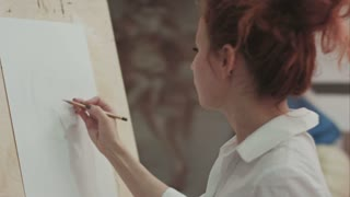 Young woman painter making sketches on blank canvas in artist workshop