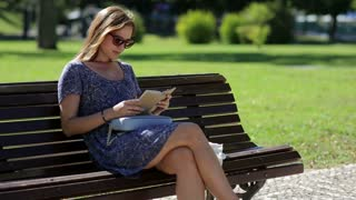 Young woman reading a book and sitting on a bench outside in a park in summer, in sunglasses