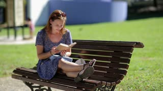 Young woman relaxing, reading a book and sitting on a bench with legs outside in a park in summer, bird in background