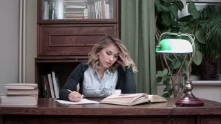 Young woman sitting at desk tired of working and taking her head in hands
