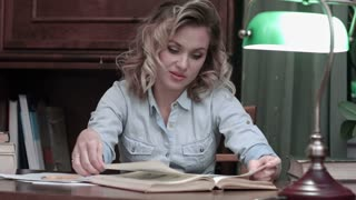 Young woman thoughtfully studying the book on her desk