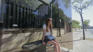 Young woman waiting and talking by phone at glass bus stop in skirt and with handbag, summertime