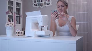 Young woman with phone sitting at the table next to sewing machine