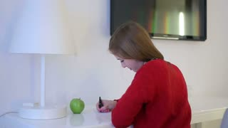 Young woman writes to notepad on a white table