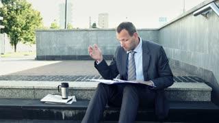 0verwhelmed, sad businessman by too much paperwork