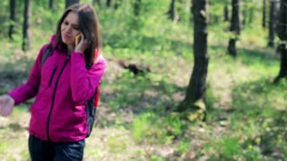 A lost woman talking on cellphone and looking for direction in the forest