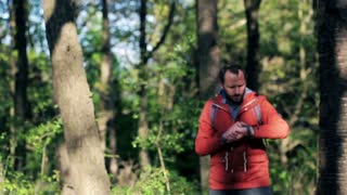 A lost young man with smartwatch looking for direction in the forest