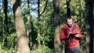 A lost young man with tablet looking for direction in the forest