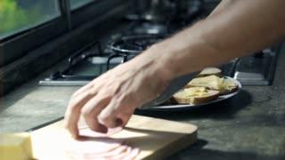 an cutting ham and preparing sandwich in kitchen, focus on hands
