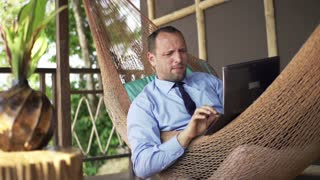 Angry businessman destroying laptop while lying on the hammock on terrace, 240fps