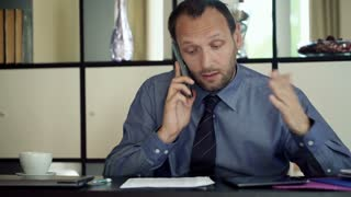 Angry businessman with cellphone and documents by desk in the office