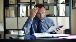 Angry, overwhelmed businessman reading documents by desk at home