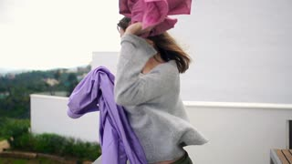 Angry, young woman throwing away clothes her man from terrace, slow motion