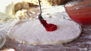 applying tomato sauce on the pizza