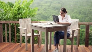 Attractive woman with tablet computer sitting by table on terrace