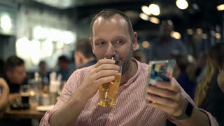 Attractive, young man drinking beer and using smartphone in cafe