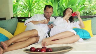 beautiful couple relaxing with smartphone on gazebo bed in garden