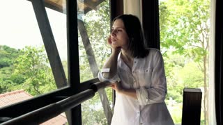 Beautiful, pensive woman looking through the window with beautiful view