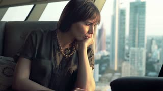 Beautiful, sad woman sitting in a cafe with city view