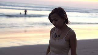 Beautiful sad woman walking on the beach during sunset, shot at 240fps