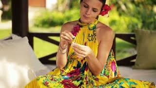 beautiful woman doing nails on gazebo bed in garden