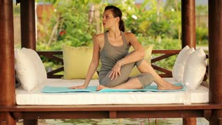 beautiful woman doing stretching exercise on the gazebo bed in  garden