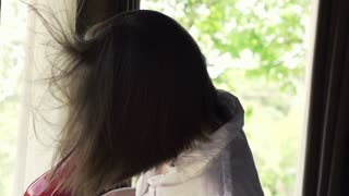 Beautiful woman drying her hair standing near a window, super slow motion, shot at 240fps