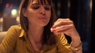Beautiful woman eating snack in cafe at night
