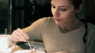 Beautiful woman eating tasty cake at cafe