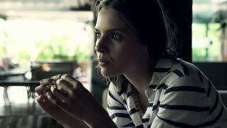 Beautiful woman eating tasty cookies in cafe