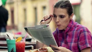 Beautiful woman reading magazine and eating salad in cafe in city
