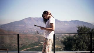 Beautiful woman reading newspaper on terrace in the country