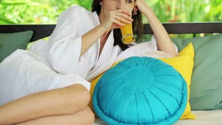 beautiful woman relaxing with cocktail on gazebo bed in garden