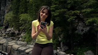 Beautiful woman sitting with smartphone on the bridge close to the stream in the forest, 240fps