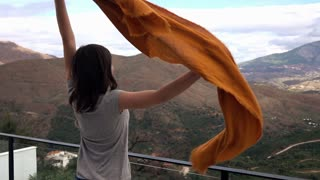 Beautiful woman throwing her scarf standing on terrace with mountains view 4K