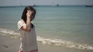 Beautiful woman walking along beach, slow motion shot at 240fps
