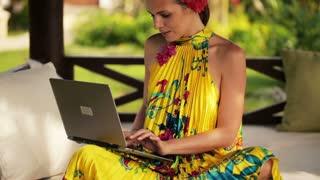 beautiful woman working on laptop in the gazebo garden