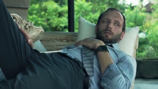 Bored, young businessman lying on wooden sofa on terrace