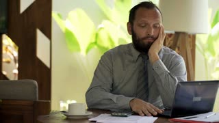 Bored, young businessman sitting by table at home