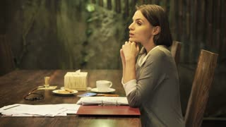 Bored, young businesswoman sitting by table at home at night