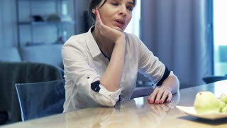 Bored, young businesswoman sitting by table at home