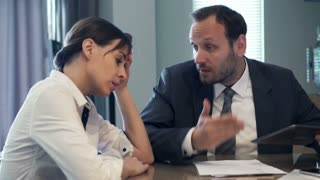 Boss with tablet yelling at businesswoman by the table in the office